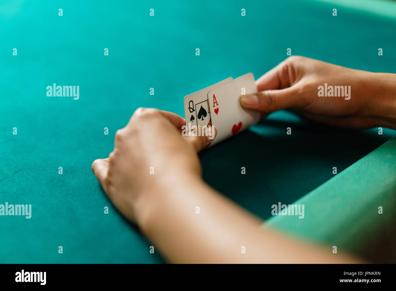 Player peeking cards in Blackjack game - Stock Image
