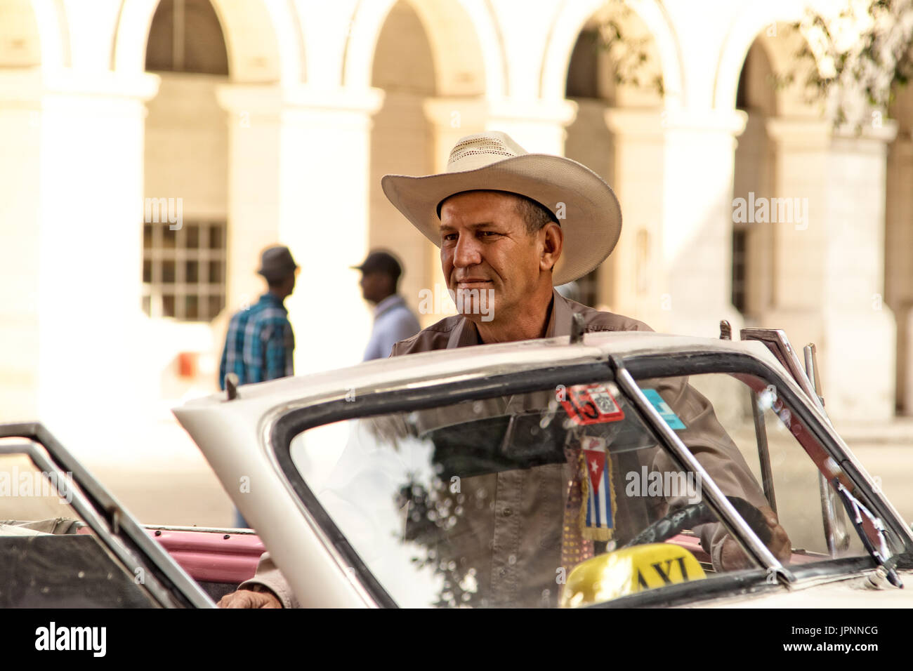 A Cuban man waits by his car for a passenger in Havana, Cuba - Stock Image