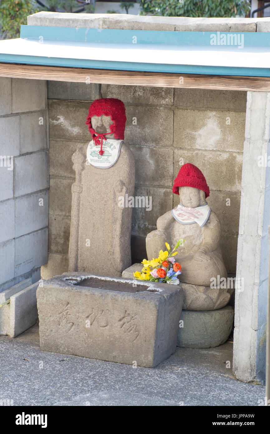 A shrine with Ojizosama statues adorned with crocheted red hads and bibs. The statues are protectors of women, travelers and deceased children. - Stock Image