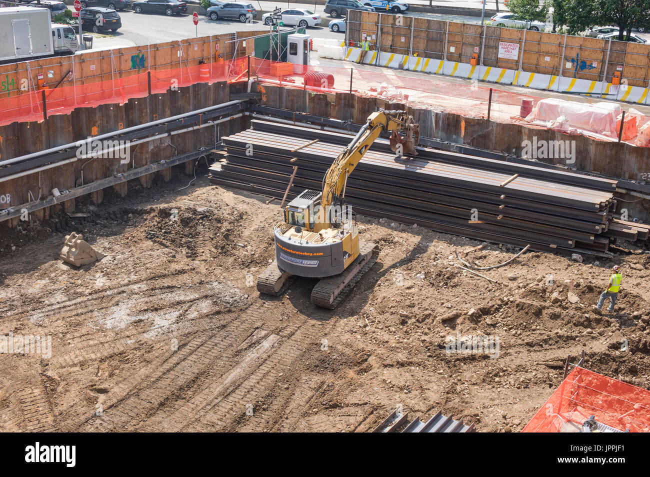 A tracked bucket excavator used as a rotating grab mover with continuous tracks and lifting crane on a construction site in New York City - Stock Image