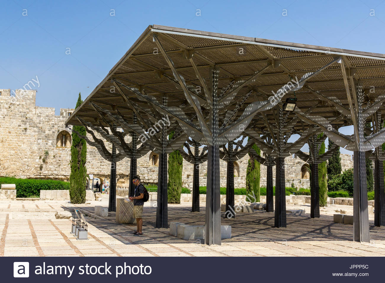 A tourist pauses in the shade at the Jerusalem Archaeological Park at the southern end of the Temple Mount in Jerusalem, Israel. - Stock Image