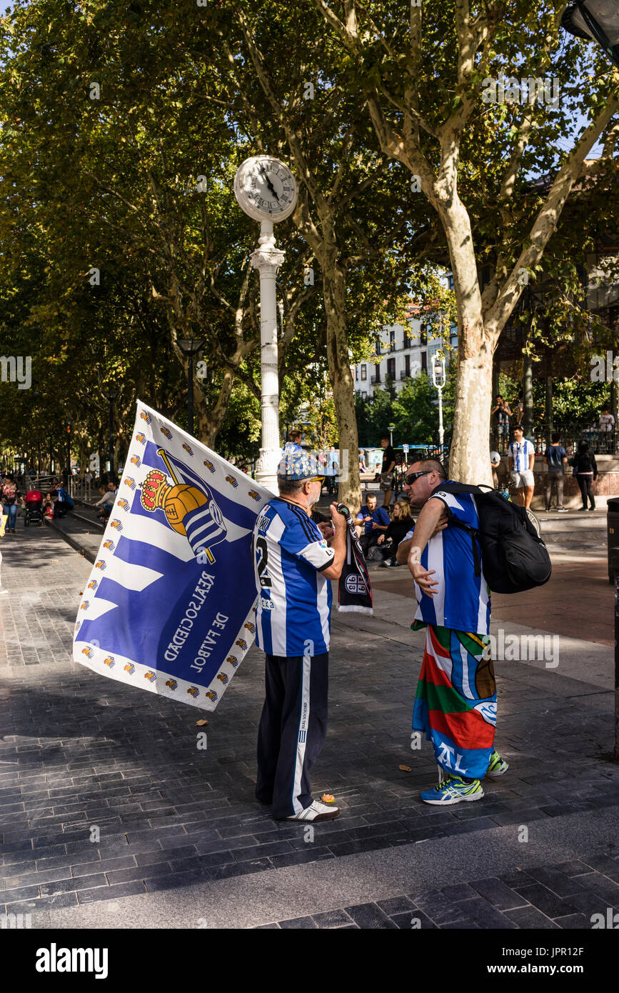 Real Sociedad supporters on their way to Anoeta Stadium, to play the Derby against Athletic Bilbao. Dressed with Home Jerseys and Basque flags - Stock Image