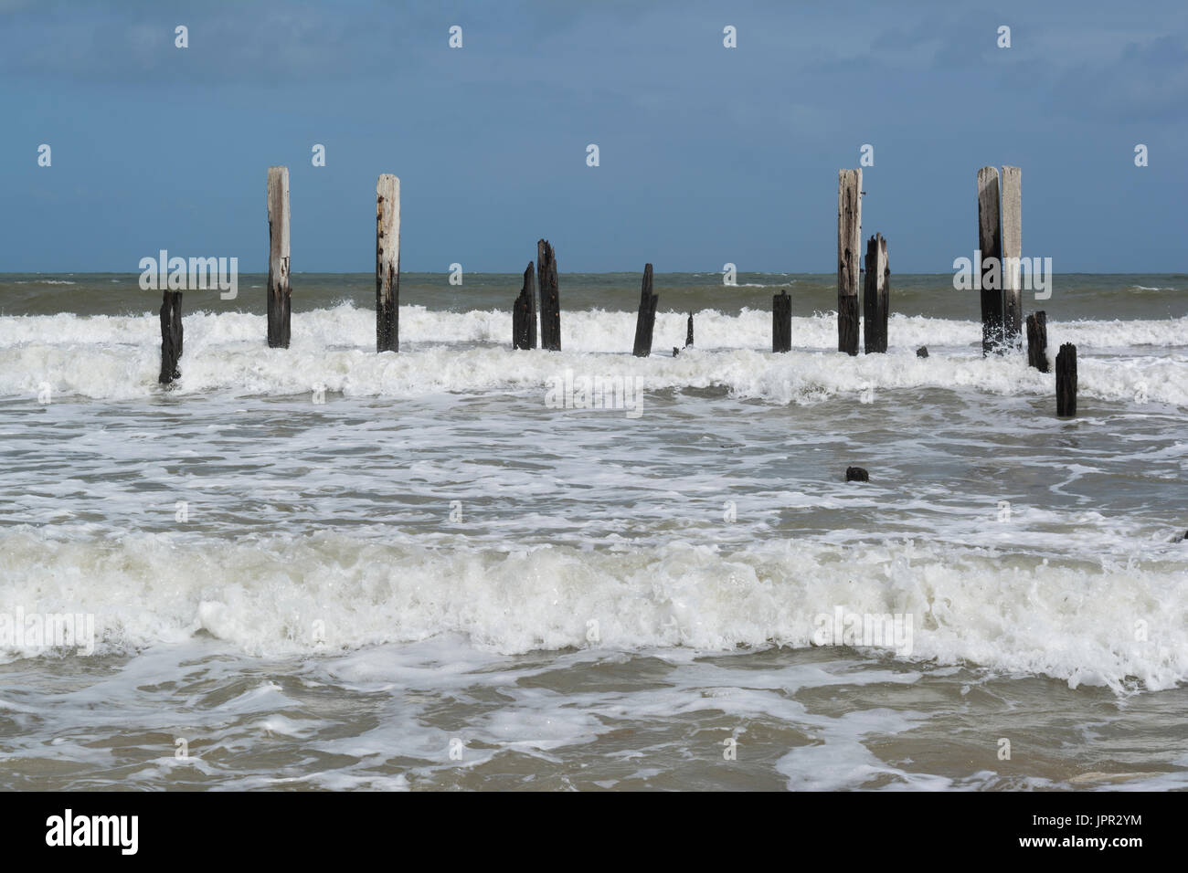 Crashing waves and high tide at Port Willunga Beach, featuring the jetty ruins affectionately called the sticks Stock Photo