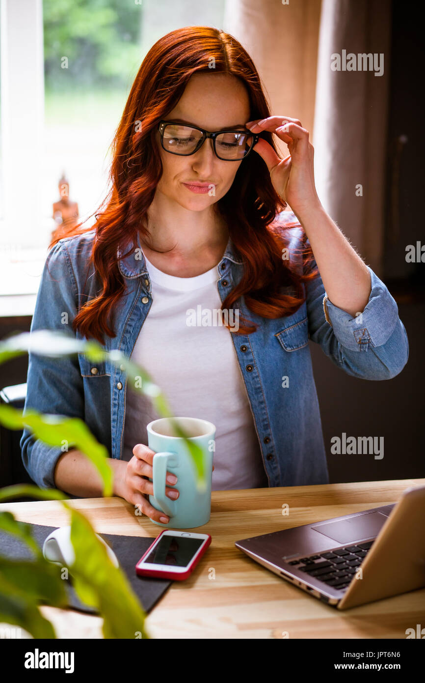 Freelancer woman at working plece showing emotion of dissatisfaction. Young foxy female correcting glasses, and holding cup. Toned image. - Stock Image