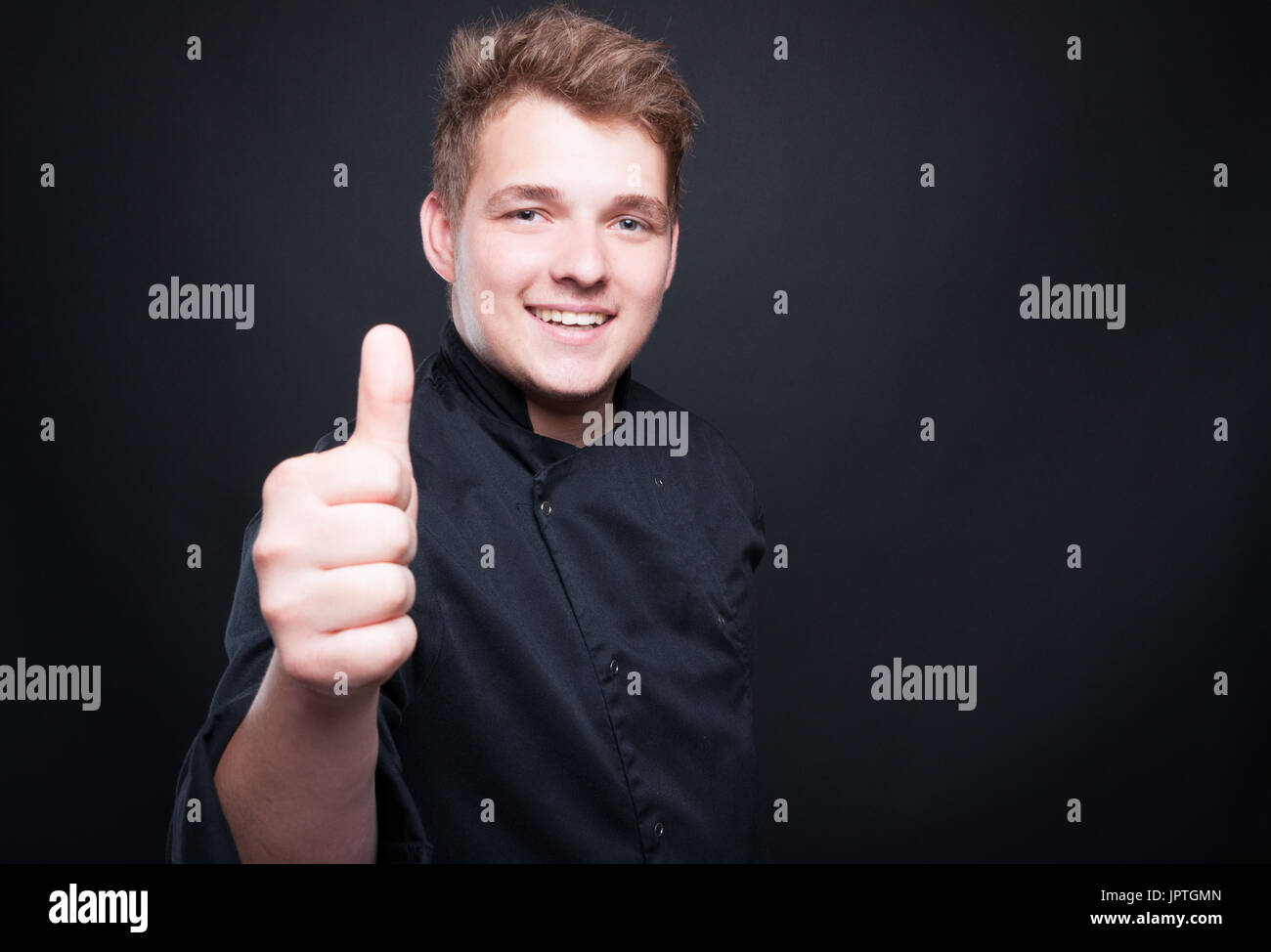 Seuccessful male chef showing like sign with right hand on dark background - Stock Image