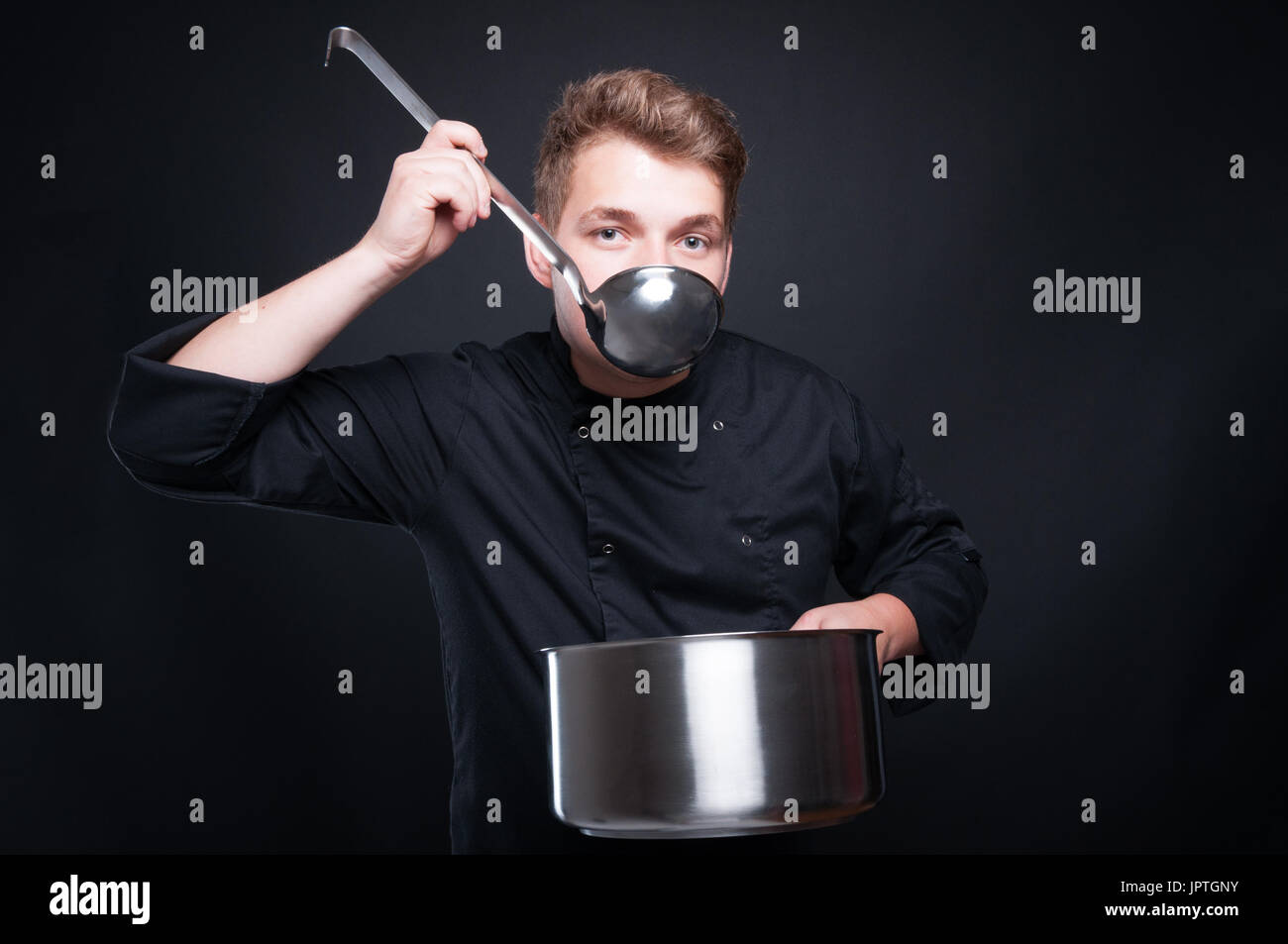 Male chef in uniform tasting his fresh soup from ladel on dark studio background Stock Photo