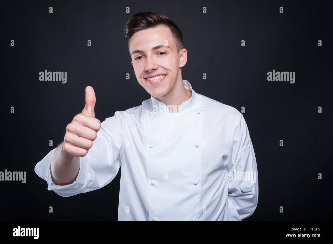 Handsome smiling chef giving thumb up for his restaurant isolated on dark background - Stock Image