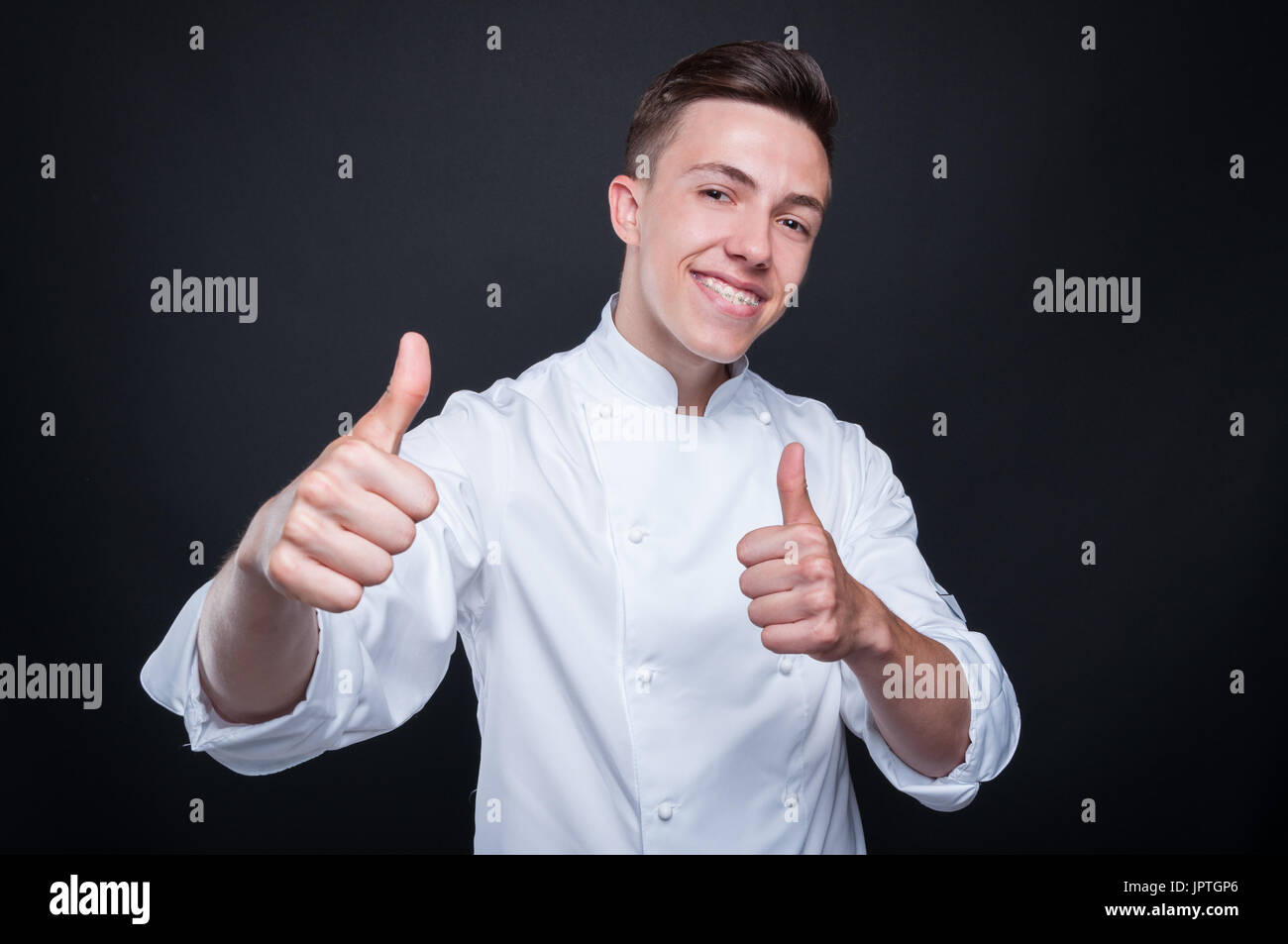 Happy successful cook looking confident and  indicate double like sign on black background - Stock Image