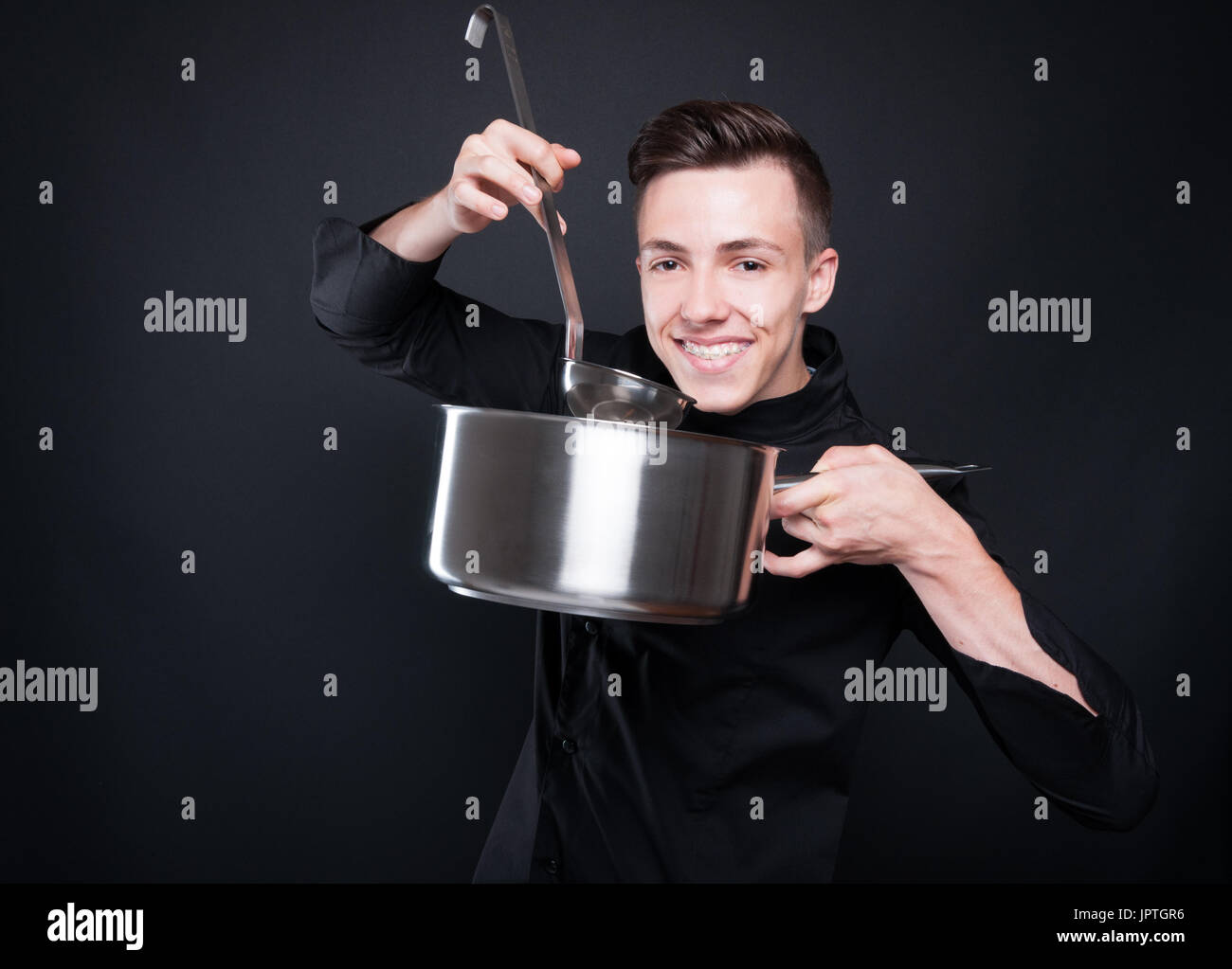 Happy chef man making delicious soup in silver pot isolated on black background Stock Photo