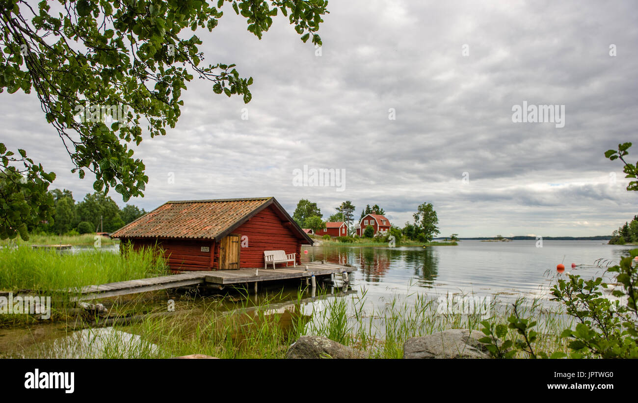 The old timbered boat-house with the liars bench on the bridge in the northern part of Stockholm archipelago, Bjorko-Arholma, Marum - Stock Image