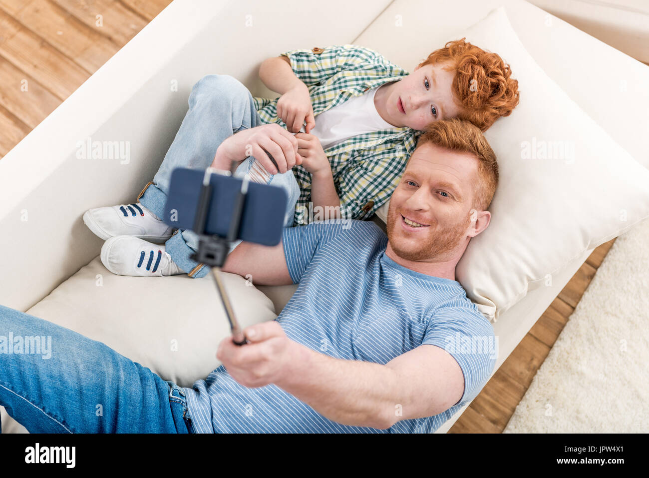 Smiling father and son lying on sofa and taking selfie with smartphone, family fun at home concept - Stock Image