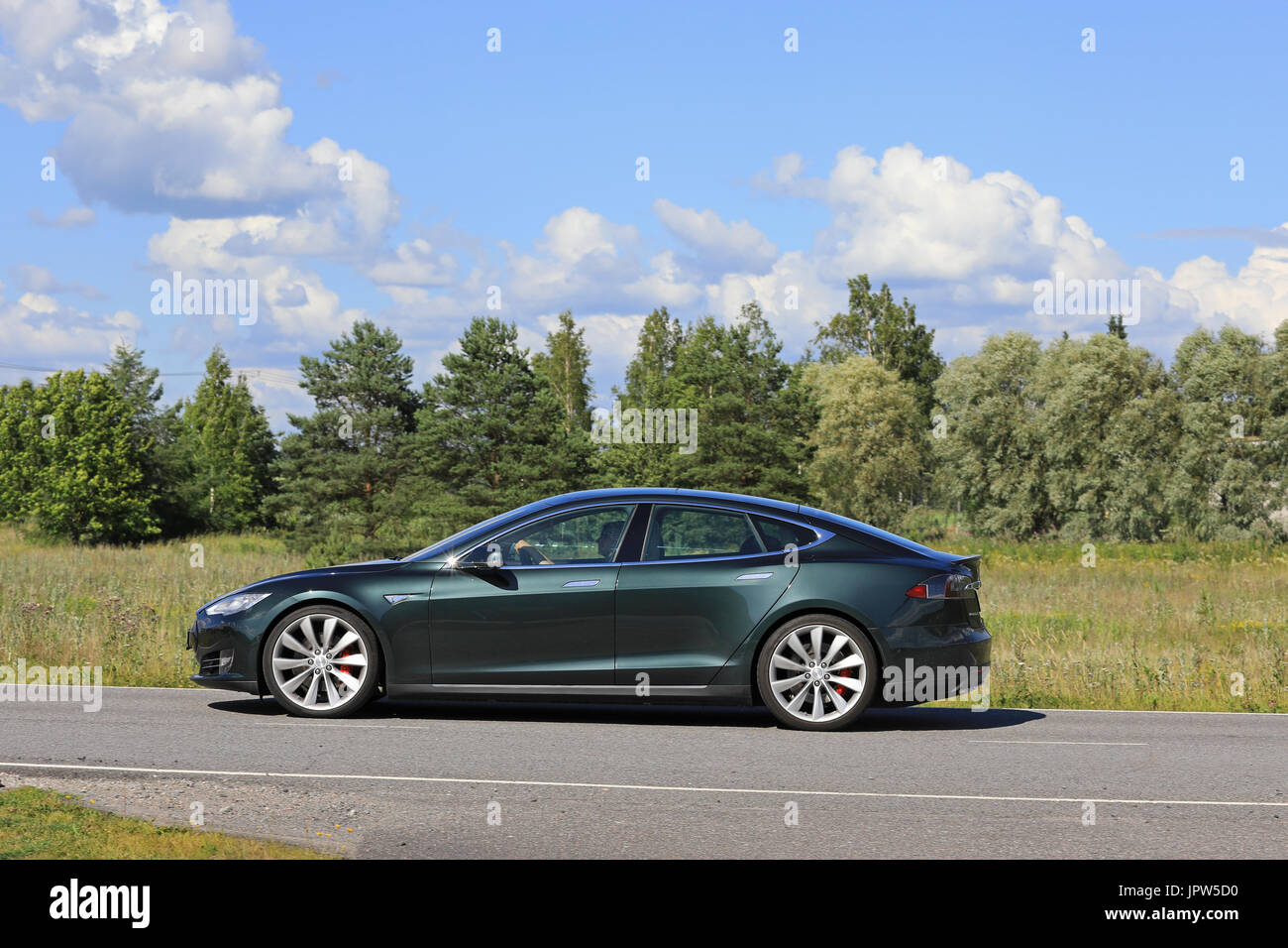 PAIMIO, FINLAND - JULY 29, 2017: Metallic green Tesla Model S moves along rural road at summer with forest and beautiful sky on the background. - Stock Image