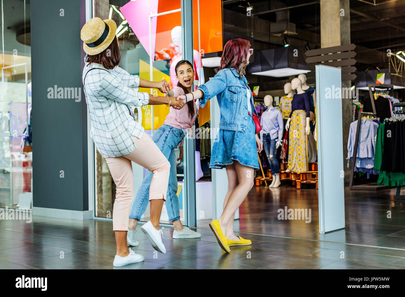 cheerful multicultural hipster girls in shopping mall, friends shopping concept - Stock Image