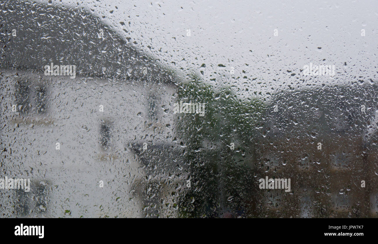 Looking through a raindrop covered window at houses on a rainy summers day - Stock Image