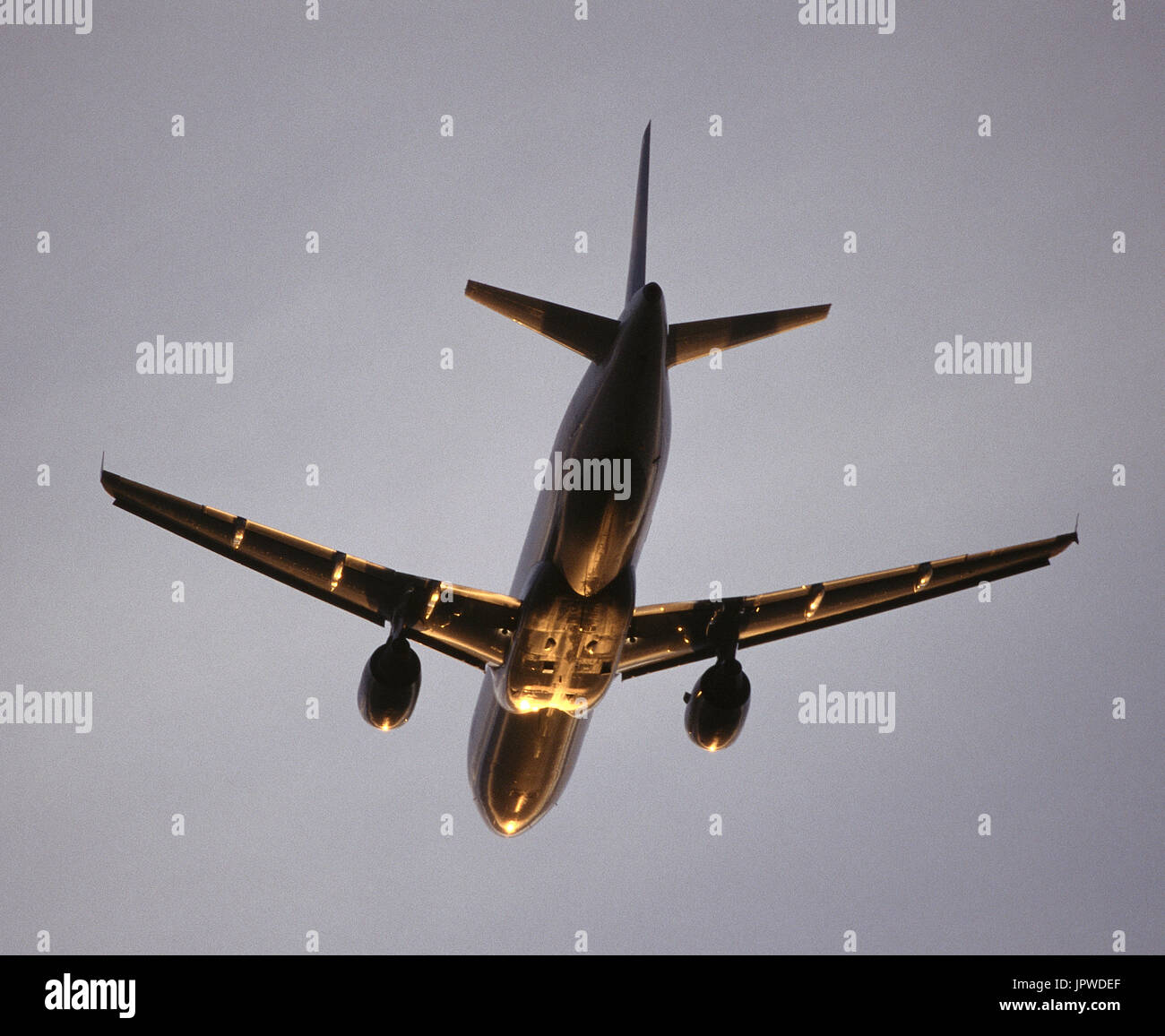 Airbus A320 flying enroute with golden light reflecting off of the fuselage underside - Stock Image