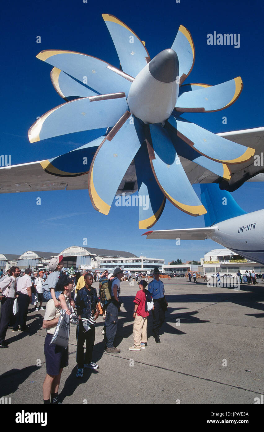 propeller blades on a Progress D-27 contrarotating propfan engine of an Antonov An-70 with people walking below at the 1999 Paris Airshow - Stock Image
