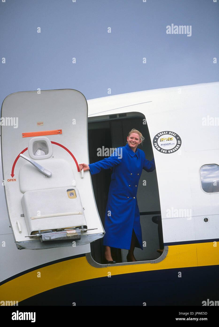 stewardess wearing blue winter overcoat closing front door of a Ryanair Boeing 737-800 & stewardess wearing blue winter overcoat closing front door of a ...