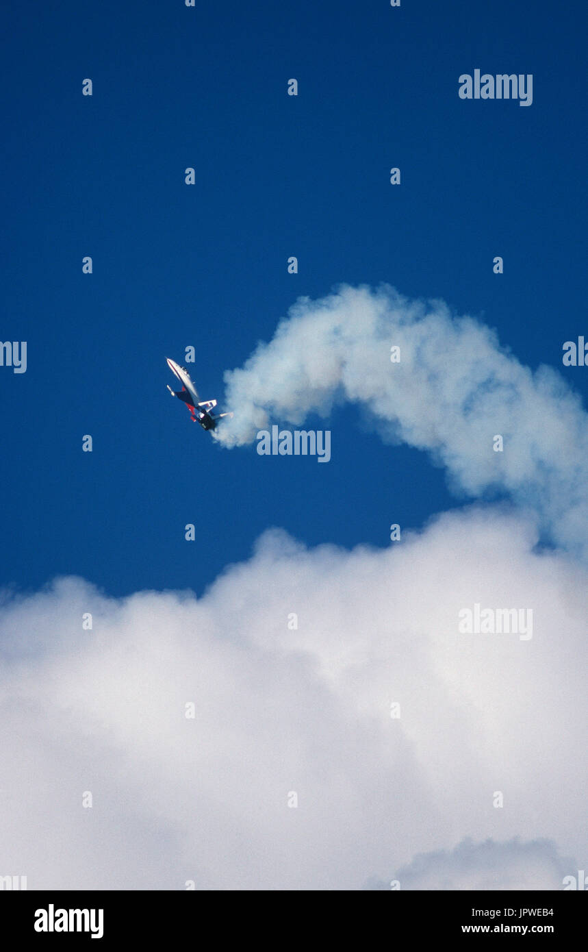 Sukhoi Su-27 Flanker in the flying-display at the 1994 Farnborough Airshow performing the Cobra manoeuvre above clouds with white smoke - Stock Image