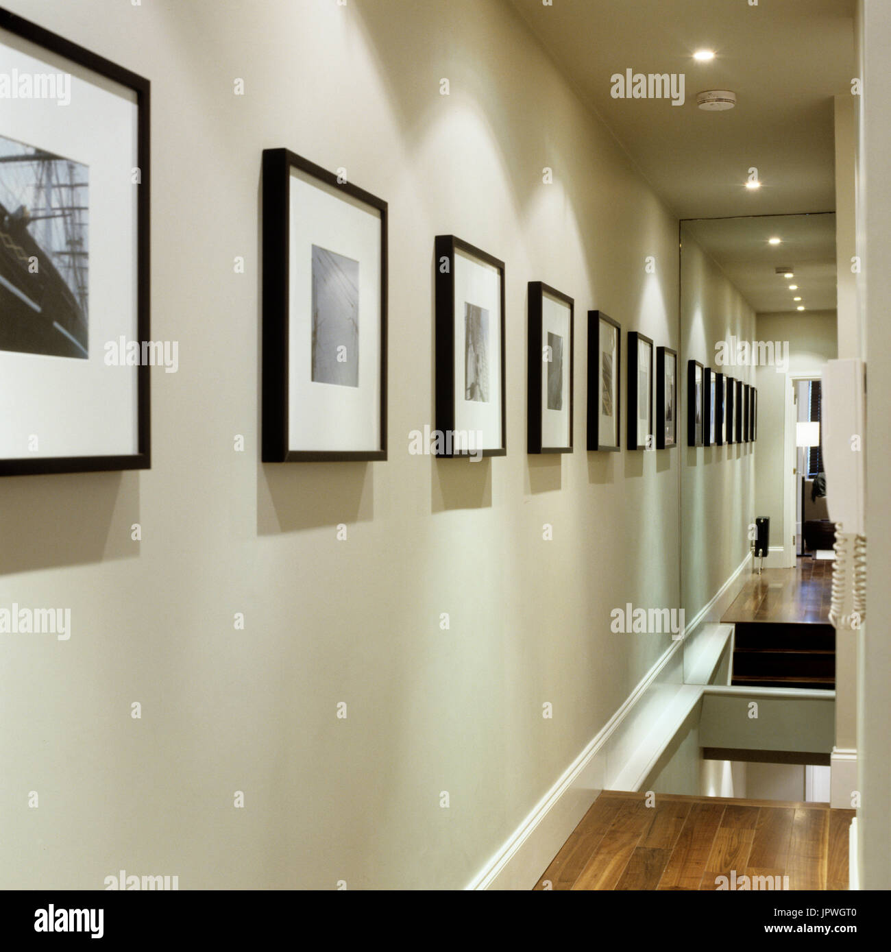 Photographs in hallway at night - Stock Image
