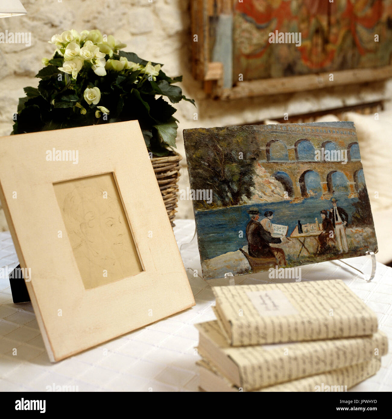 Books, frame, painting and floral arrangement on table