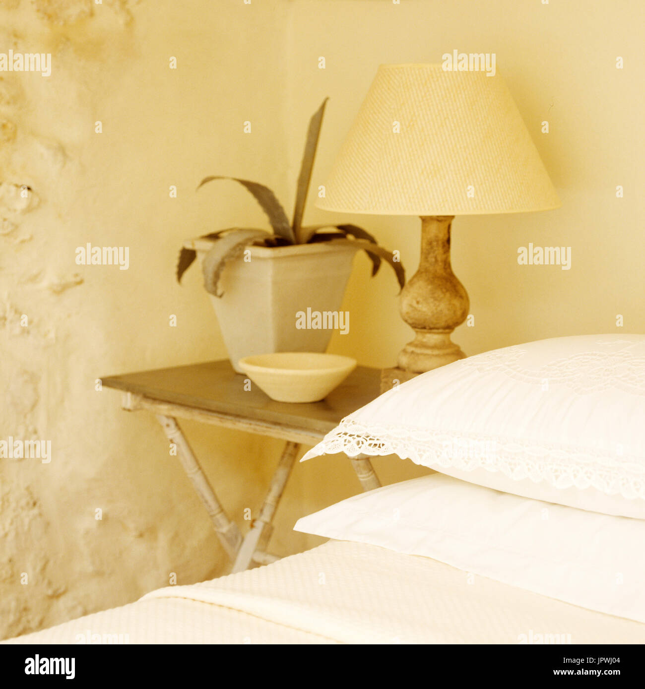 Bedside table with lamp and pot plant - Stock Image