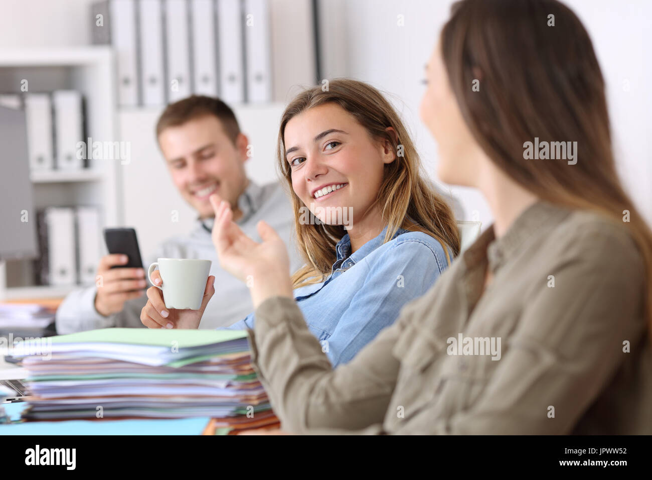 POrtrait of three lazy employees talking and wasting time sitting on a desk at office - Stock Image