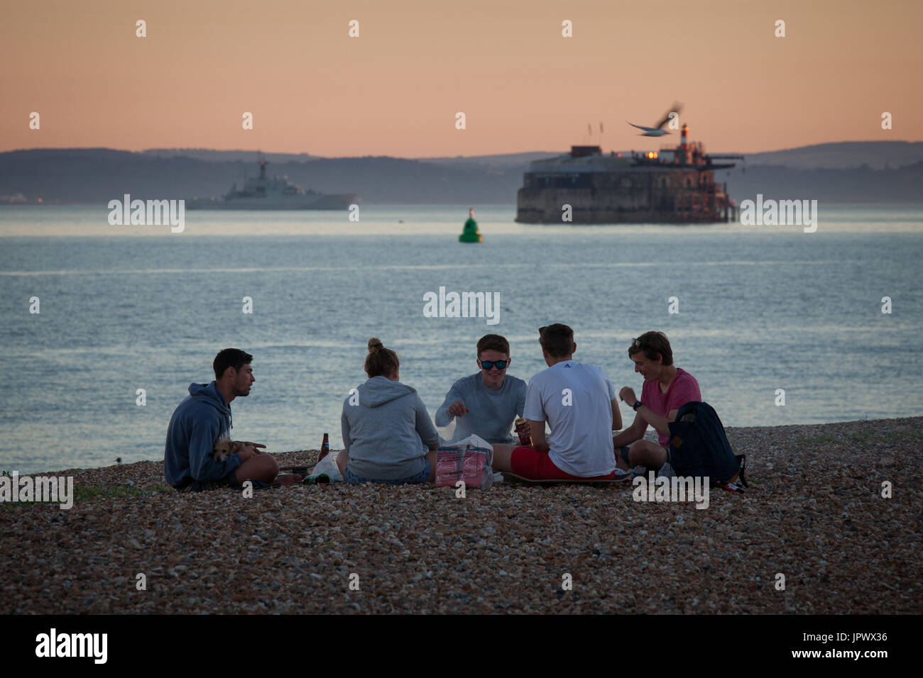 A group of young adults outdoors socialising and enjoying drinks and a barbecue on the beach in Southsea, Portsmouth. - Stock Image