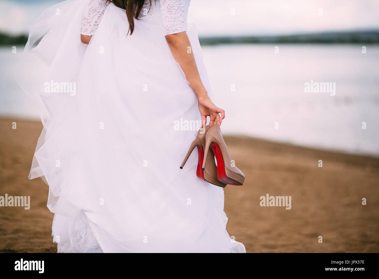 Bride looking at the sea with shoes in hands - Stock Image