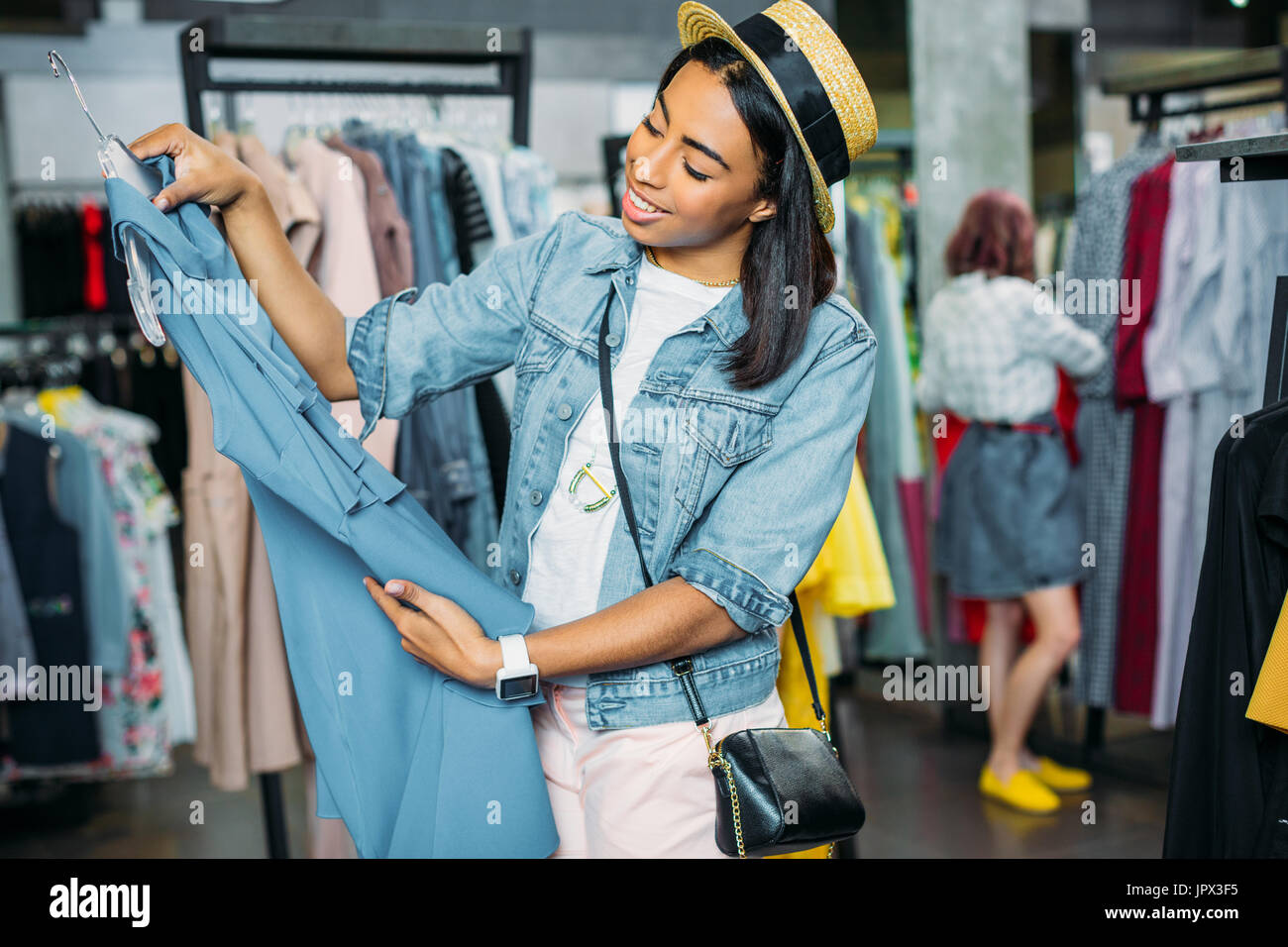 african american hipster girl choosing clothes in shopping mall, boutique shopping concept  - Stock Image