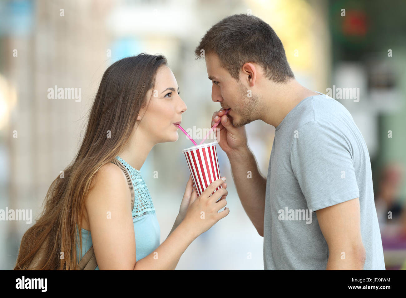 Side view portrait of a happy couple sharing a takeaway refreshment in the street Stock Photo