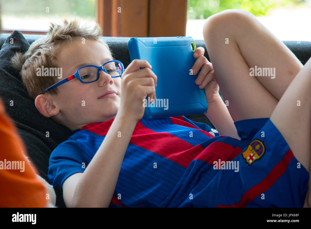 Young Boy, 6 years, playing games on tablet, close-up - Stock Image