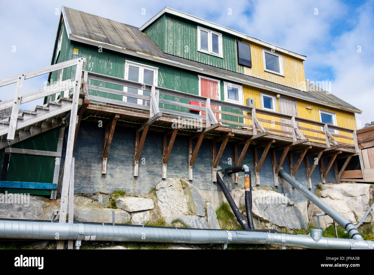 Typical Inuit houses built from wood and concrete with overground pipes for water and waste. Paamiut (Frederikshåb), Stock Photo