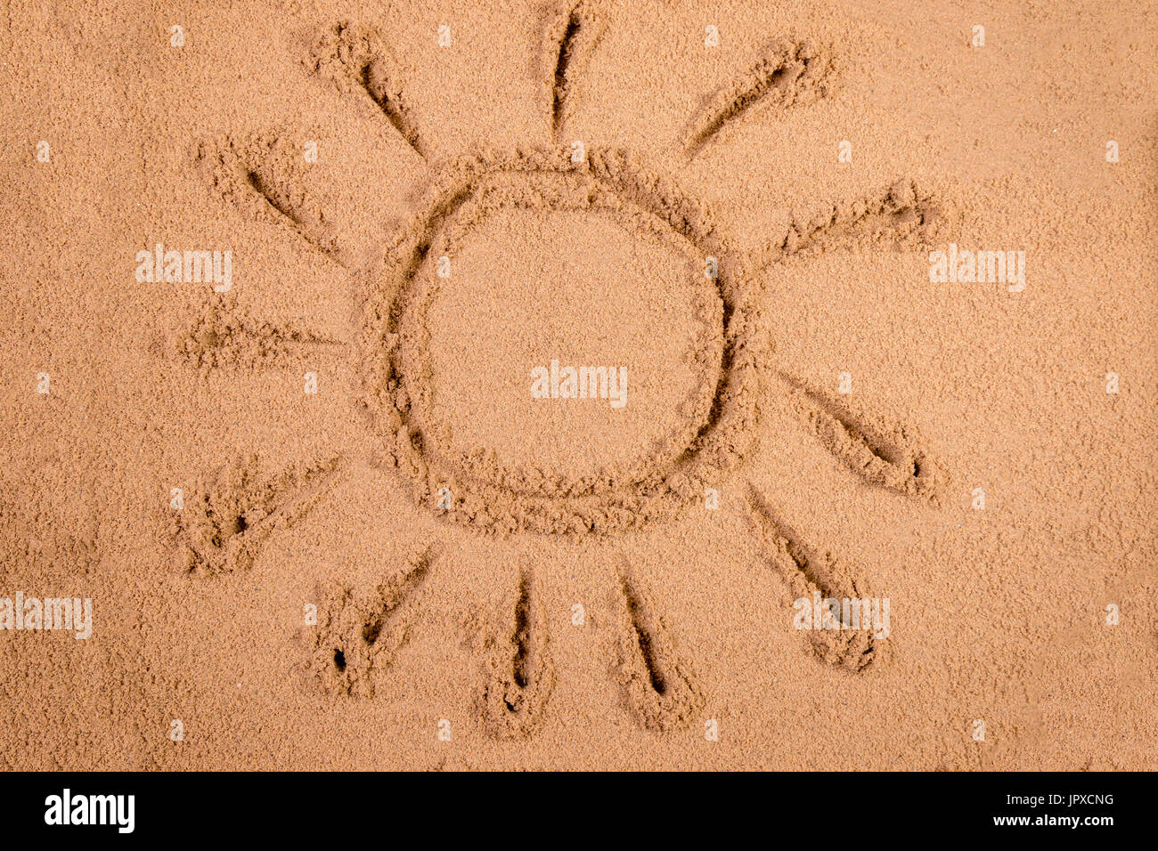 Sun drawn in soft wet sand on a beach - Stock Image