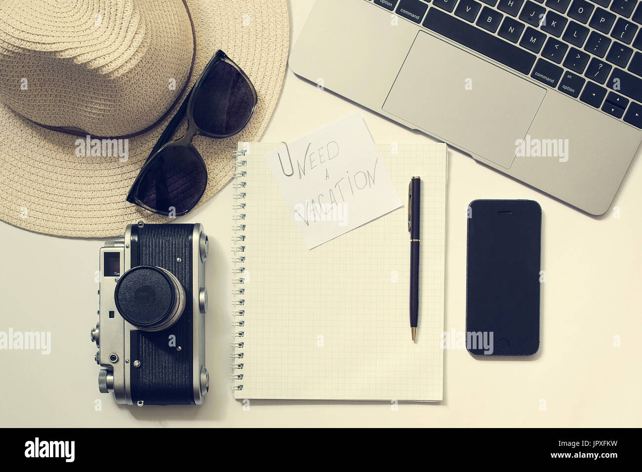 Thoughts about vacation workplace. Weekend mood. Blogger, writer or freelancer desk with laptop, open notebook, phone, pen, hat, old camera, glasses - Stock Image