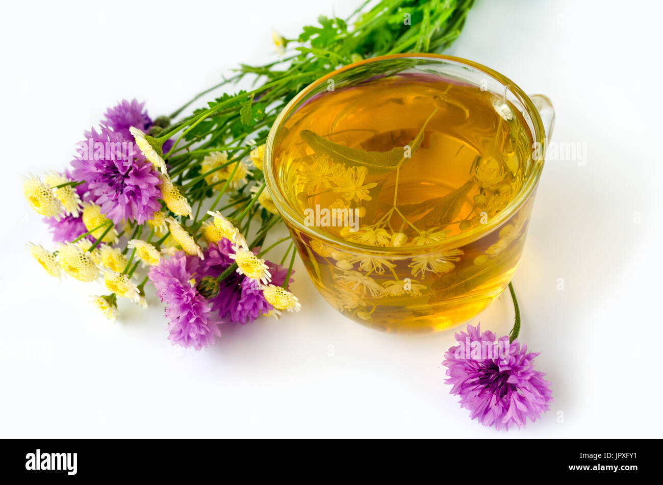 Natural therapy - Lime Tea in a transparent cup on a white background and a bouquet of wildflowers - Stock Image