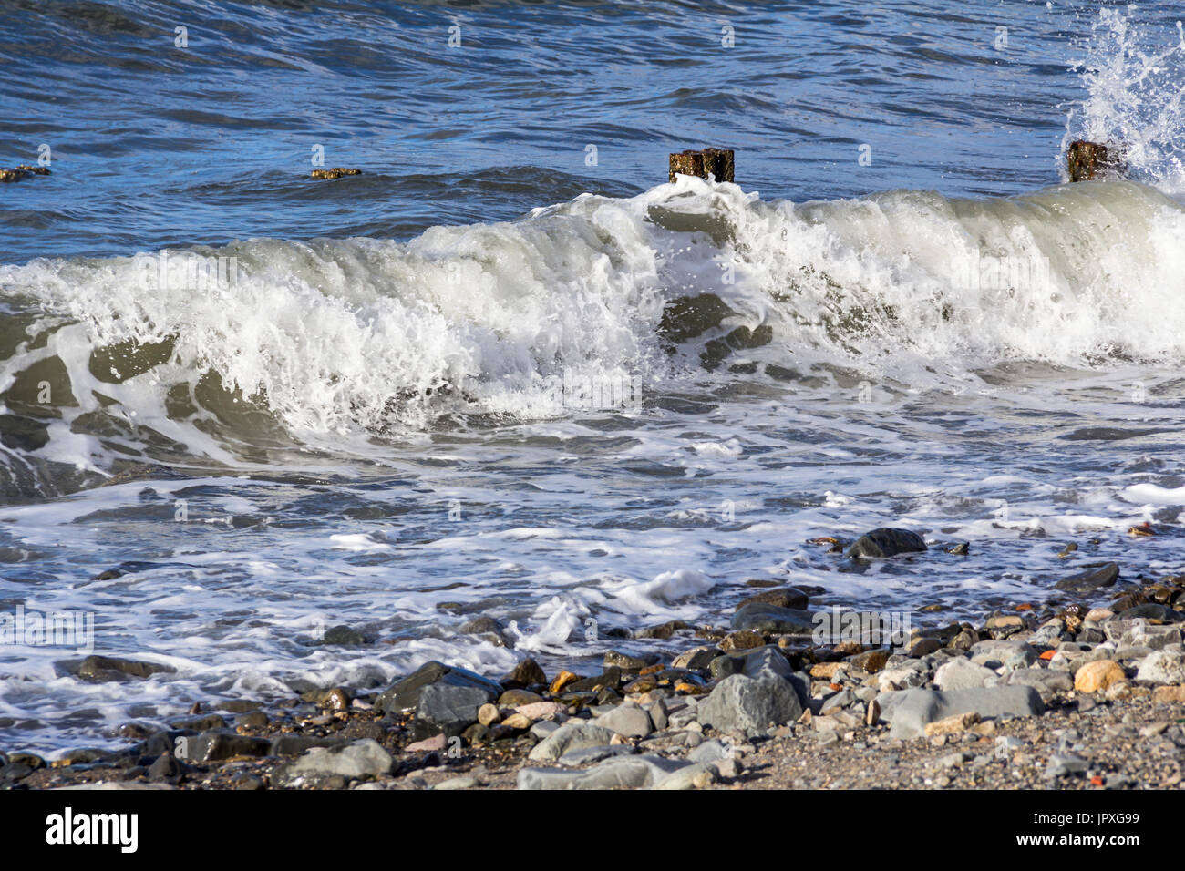 Waves rolling in over Breakwaters onto a Rocky Beach at Llanfairfechan, north Wales. The image was taken on 14 September 2013 - Stock Image