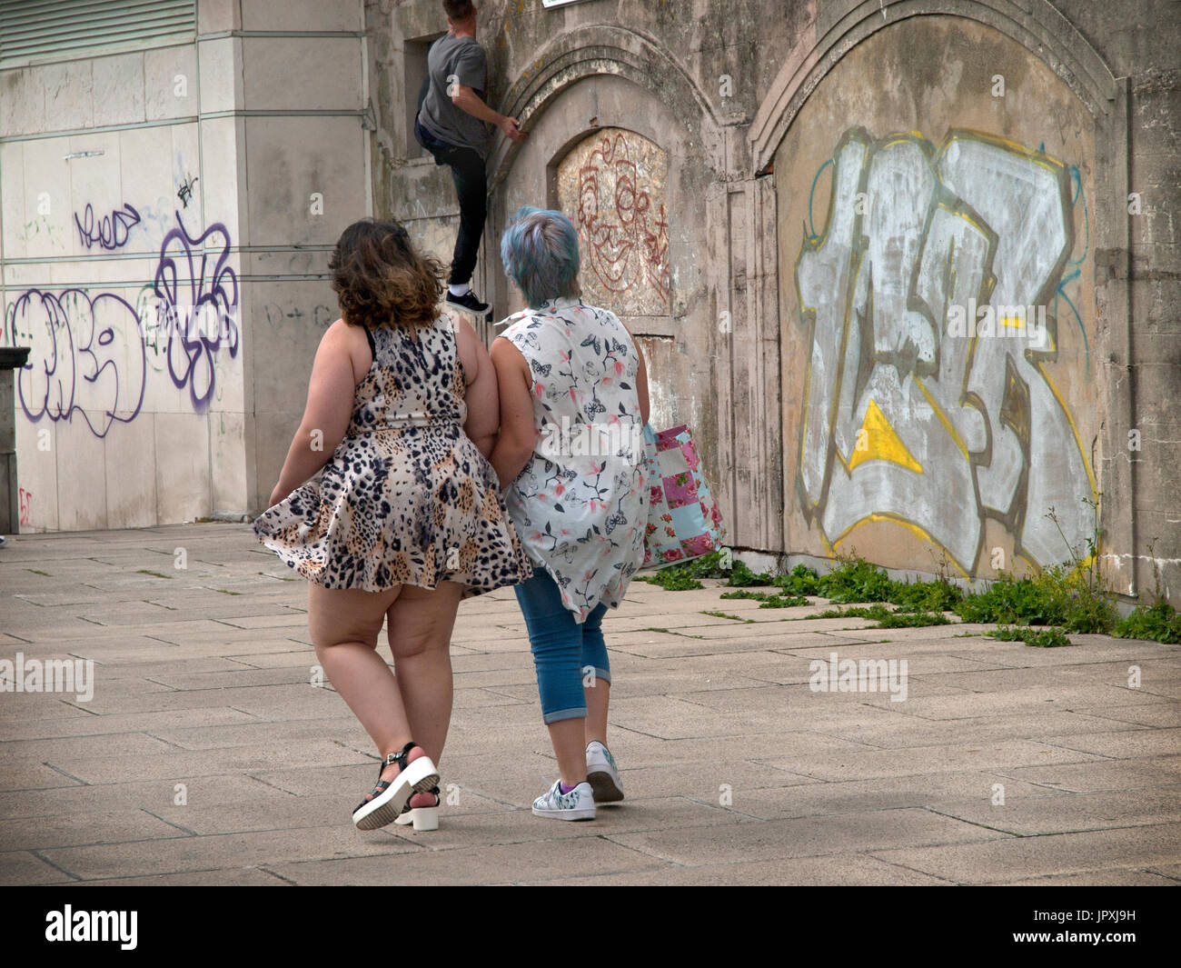 On a graffiti clad wall in Brighton a parkour enthusiast is watched climbing up a wall - Stock Image