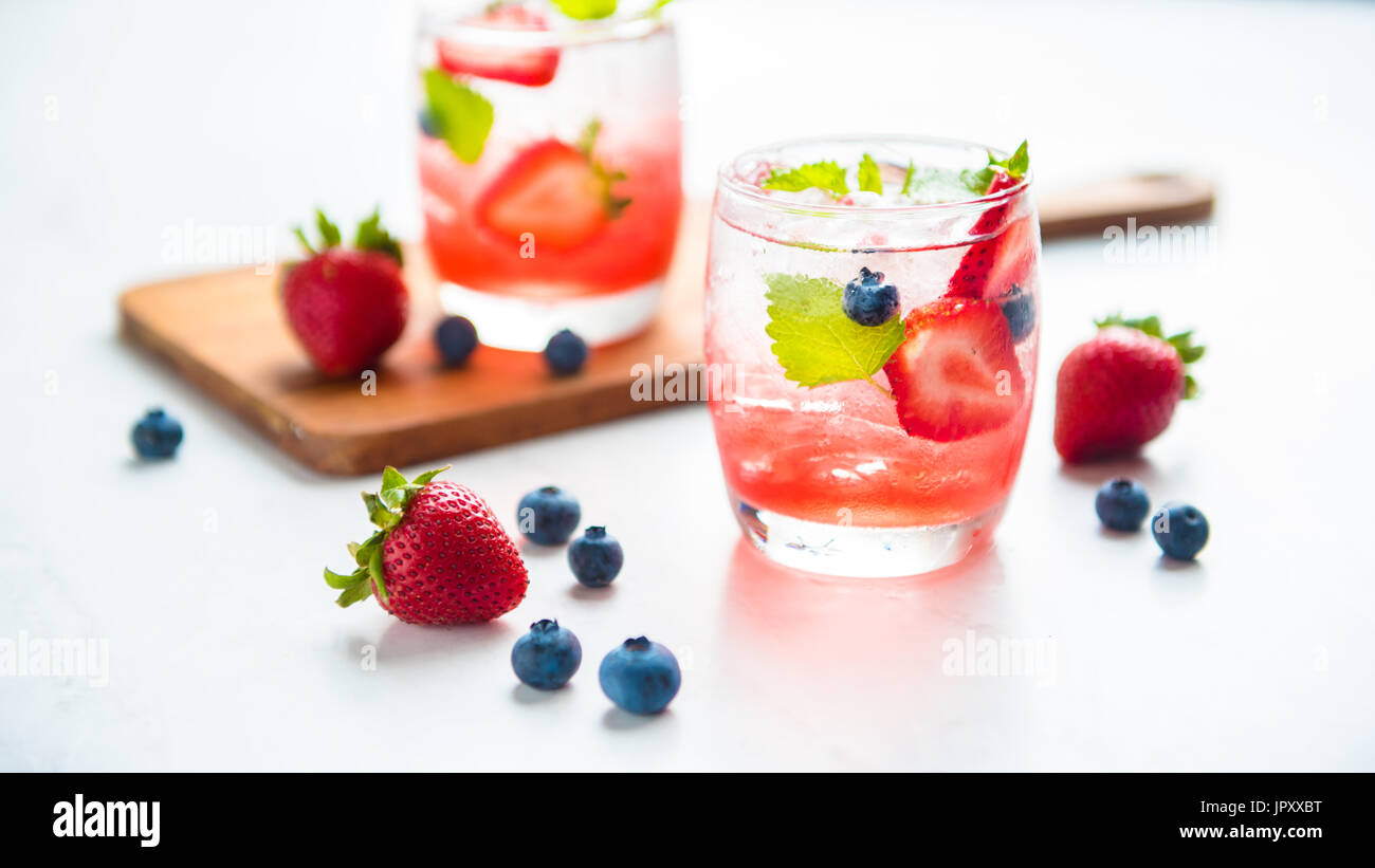 set cocktails strawberry and blueberry mix soda for healty drink but mix whisky for party enjoy - Stock Image