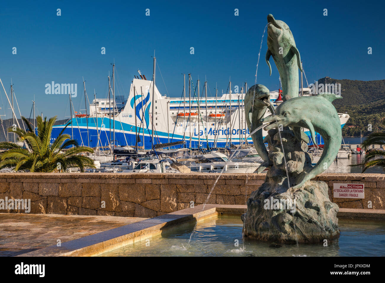 Dolphins fountain at waterfront, sailboats, M/F Kalliste ferry at pier behind, at Golfe de Valinco, Propriano, Corse-du-Sud, Corsica, France - Stock Image