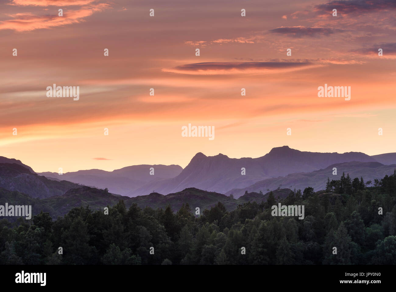 Panorama landscape of Langdale Pikes and Lakeland Fells at dusk  from the hills  above Hawkshead near Tarn Hows in the English Lake District - Stock Image