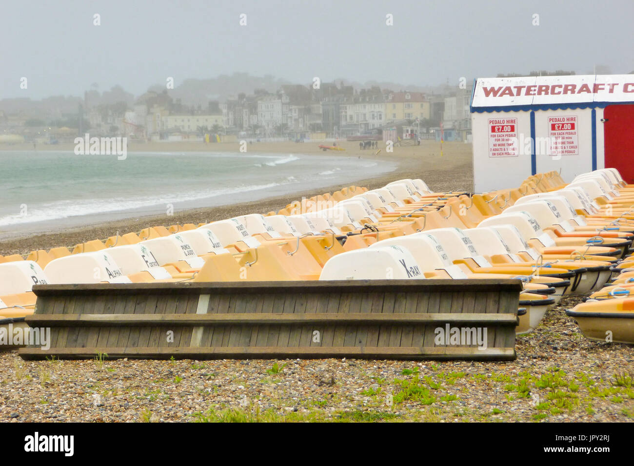 Weymouth, UK. 2nd Aug, 2017. Piles of pedalos lie, unused, on rainy Weymouth sands Credit: stuart fretwell/Alamy Live News - Stock Image