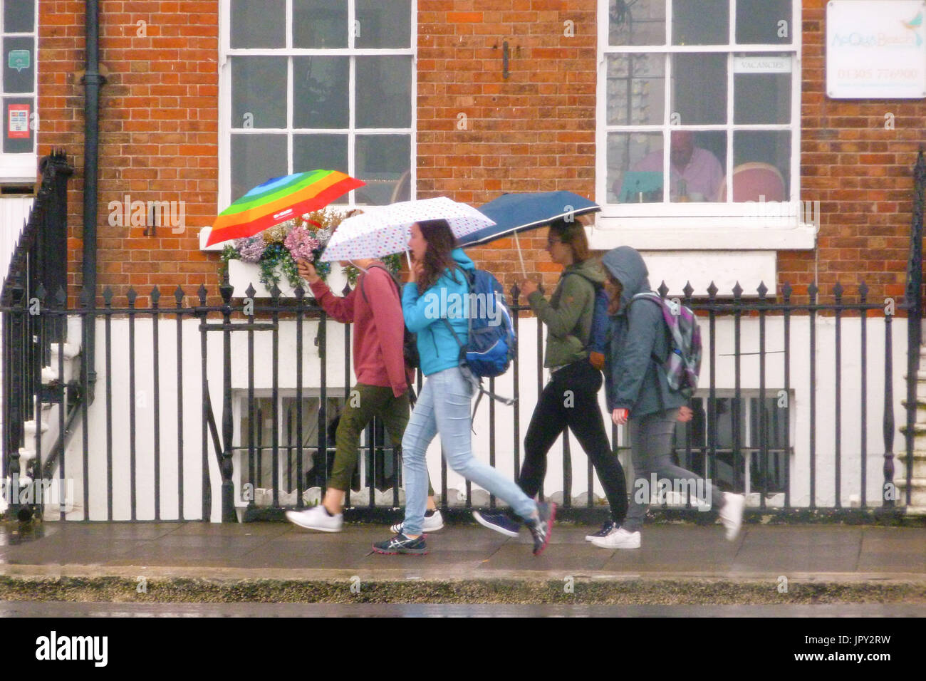 Weymouth, UK. 2nd Aug, 2017. Foreign students, here to study English, hurry to classes in the pouring rain Credit: stuart fretwell/Alamy Live News - Stock Image