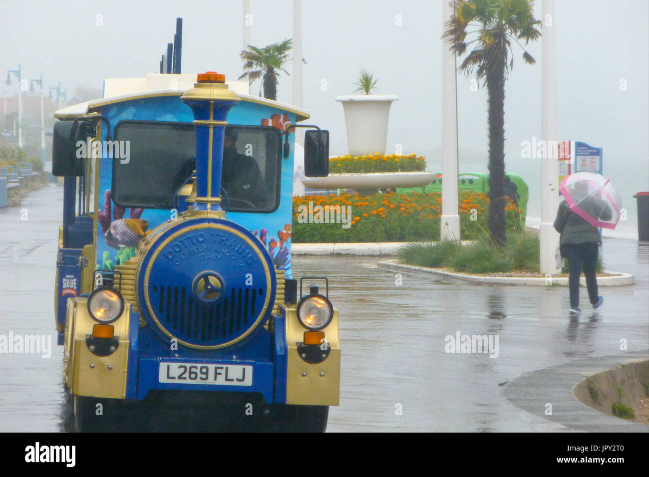 Weymouth, UK. 2nd Aug, 2017. People make the most of a day of non-stop torrential rain on Weymouth sands, with a ride along the promenade on the land train Credit: stuart fretwell/Alamy Live News - Stock Image