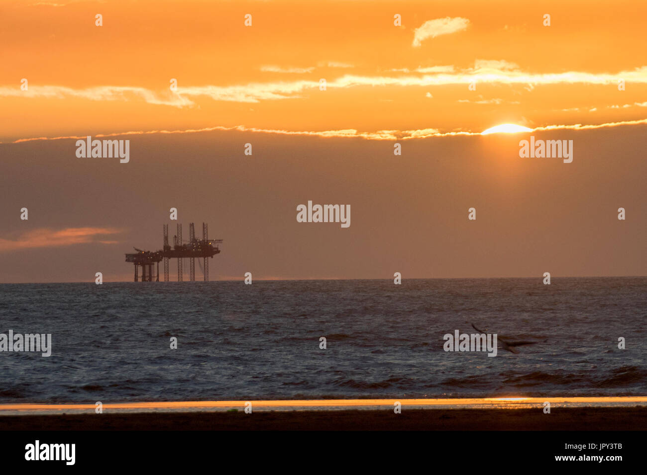 Ainsdale, Southport, Merseyside, UK. 2nd August, 2017. UK Weather.  Colourful sunset over Morecambe Bay Gas Rig. In 1974 the second largest gas field in the UK was discovered 25 miles (40 km) west of Blackpool, with original reserves of over 7 trillion cubic feet (tcf) (200 billion cubic metres). At its peak 15% of Britain's gas supply came from the bay but production is now in decline and the main field was mothballed in 2011. Credit:  MediaWorldImages/AlamyLiveNews - Stock Image