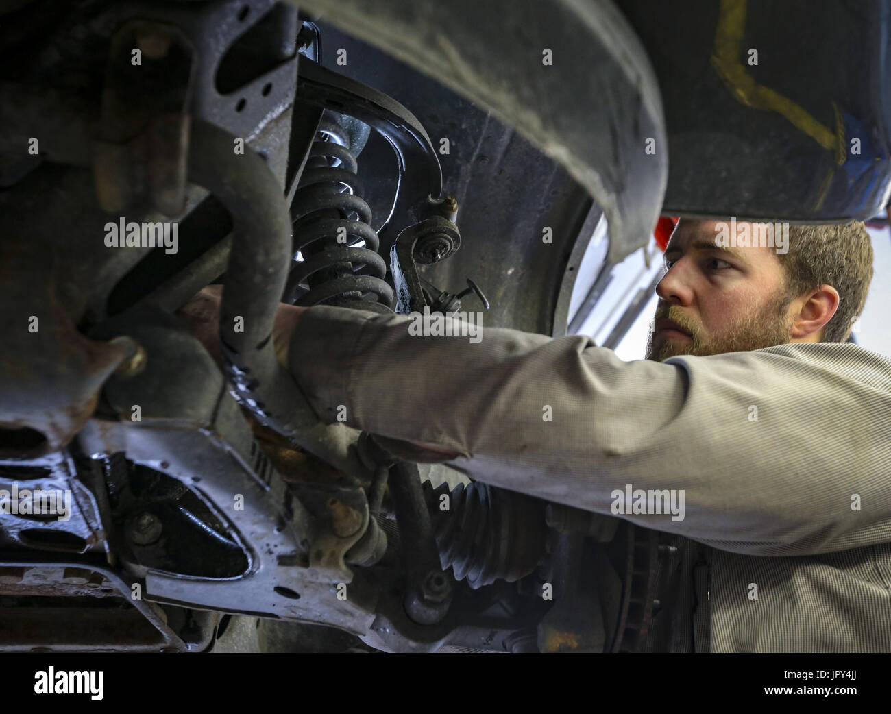 Davenport, Iowa, USA. 19th Jan, 2017. Manager Bill Dittmer reaches in through the suspension assembly of a Honda Pilot to access the thermostat at Dittmer's Service in Davenport on Thursday, January 19, 2017. In January of 2016, the family owned full-service gas station parted ways with Shell Oil Company. The four-pump station lost its big oil affiliation this when the Dittmer brothers refused to conform to the multinational oil and gasoline company's expectations. Credit: Andy Abeyta/Quad-City Times/ZUMA Wire/Alamy Live News - Stock Image