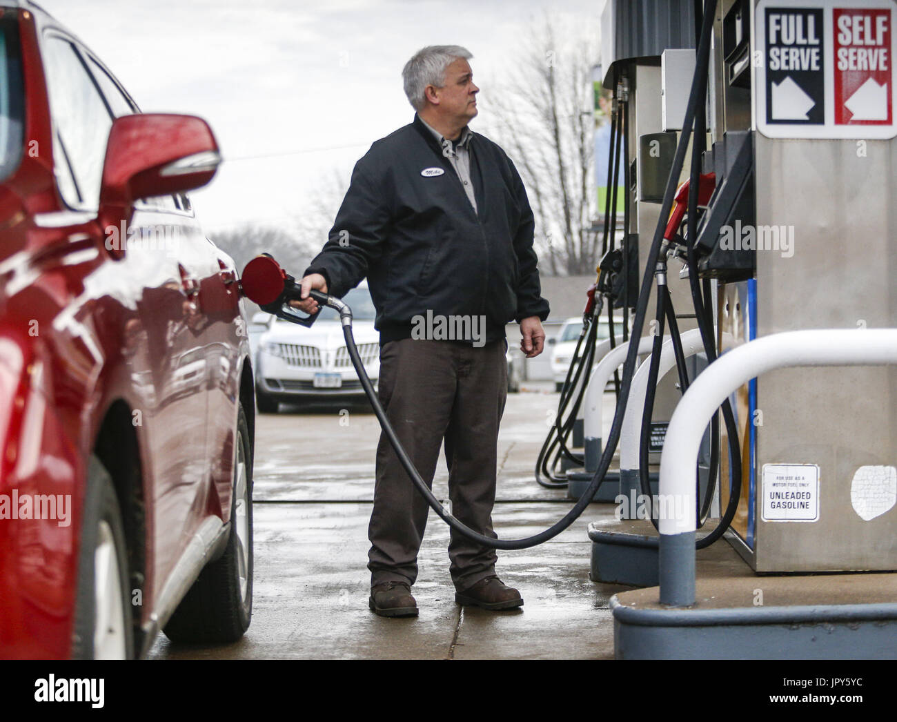 Davenport, Iowa, USA. 19th Jan, 2017. Mechanic Mike Waite fills up a customer's car with gas at Dittmer's Service in Davenport on Thursday, January 19, 2017. In January of 2016, the family owned full-service gas station parted ways with Shell Oil Company. The four-pump station lost its big oil affiliation this when the Dittmer brothers refused to conform to the multinational oil and gasoline company's expectations. Credit: Andy Abeyta/Quad-City Times/ZUMA Wire/Alamy Live News - Stock Image