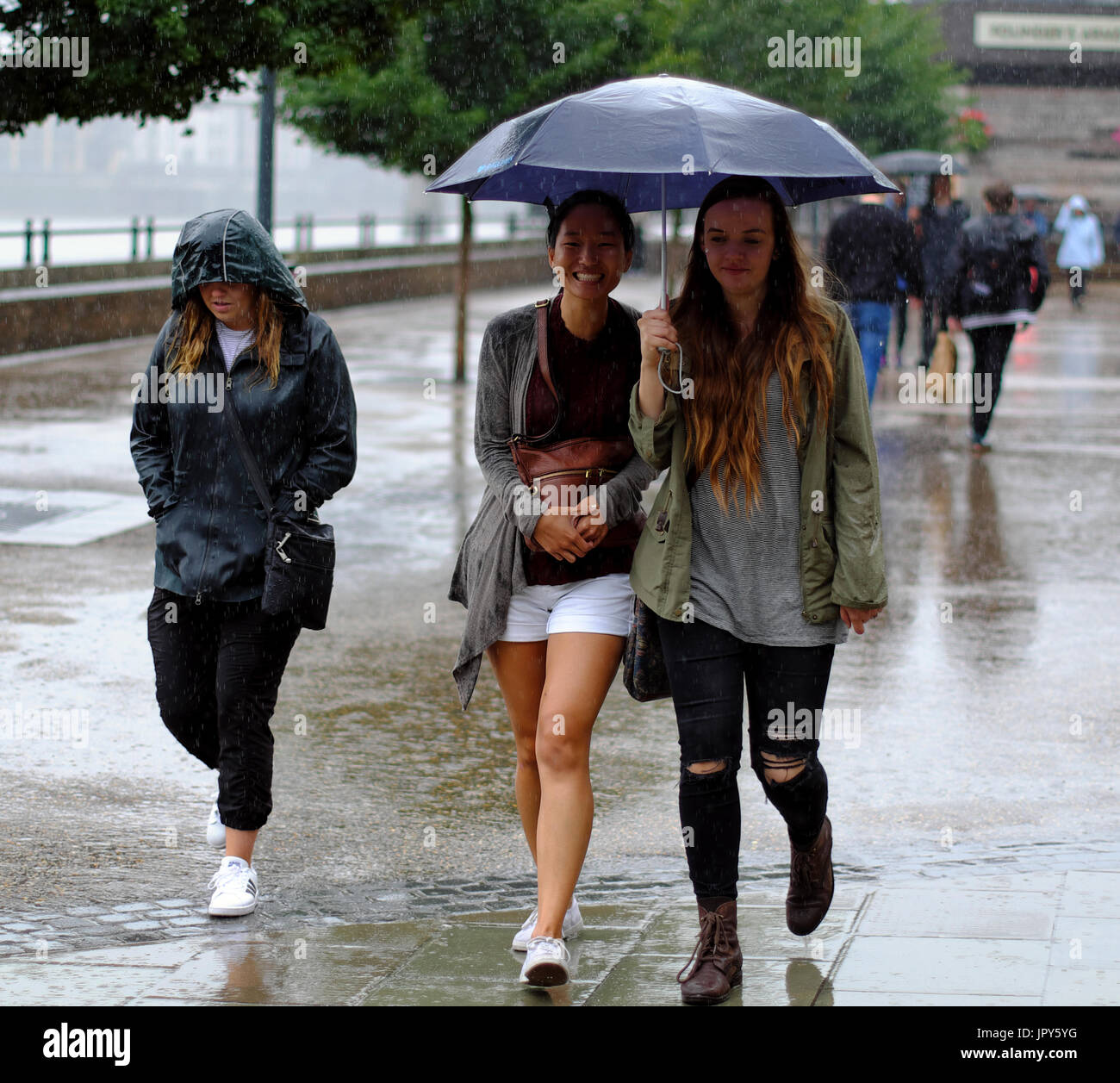 two young women sharing an umbrella whilst walking during heavy rain in London, England Stock Photo
