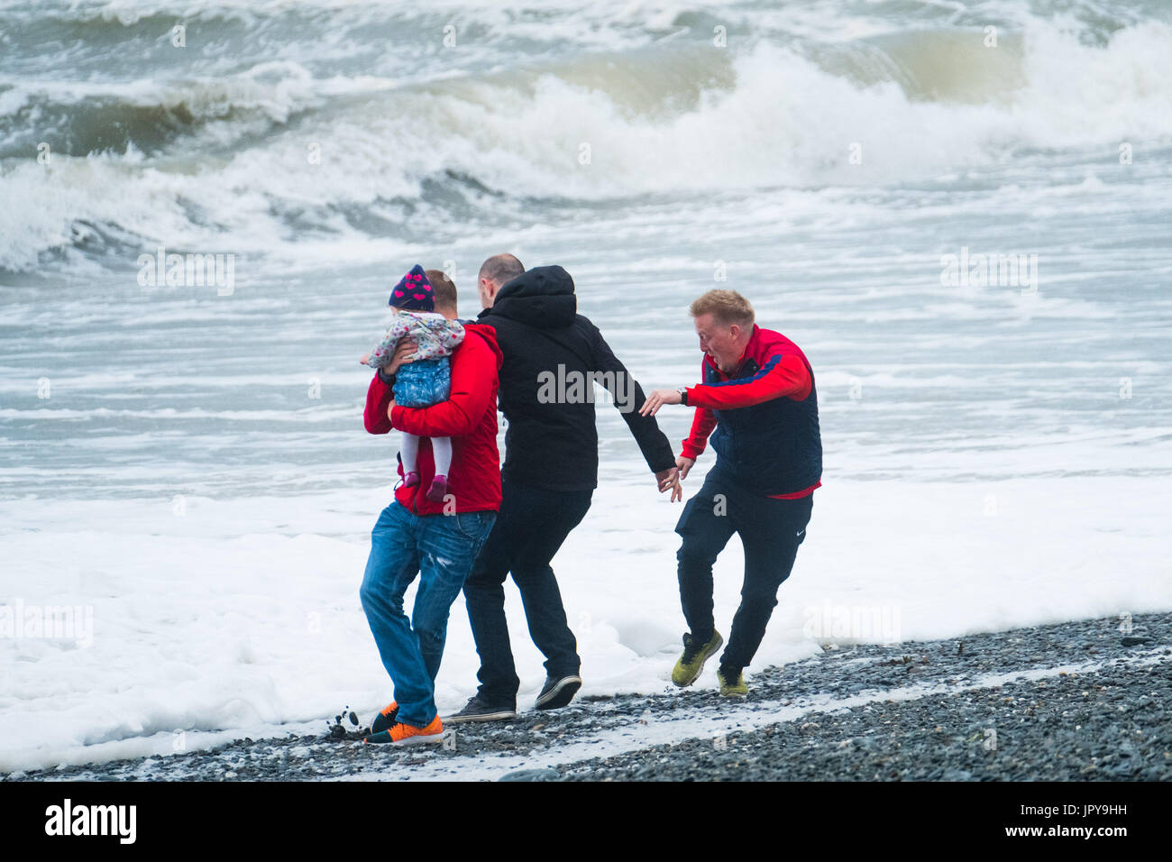 Aberystwyth Wales UK, Thursday 03 August 2017 UK Weather: A young family play a dangerous game of dodging the waves as unseasonal gale force winds and stormy seas lash the seaside at Aberystwyth on the west Wales coast. More wet and unsettled weather, caused by the jet stream flowing further south than normal, is forecast for the United Kingdom for much of the rest of the summer photo Credit: Keith Morris/Alamy Live News - Stock Image