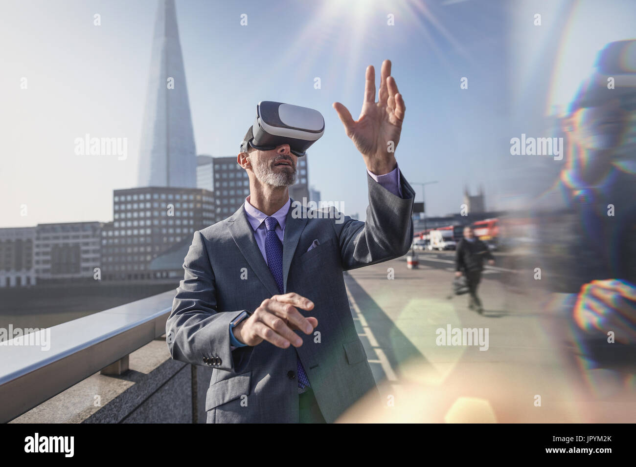 Businessman using virtual reality simulator glasses on sunny urban bridge, London, UK - Stock Image