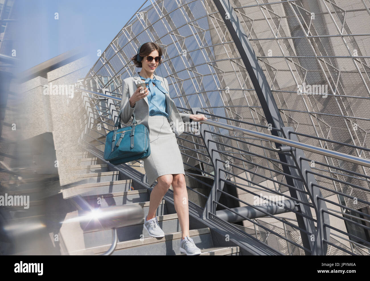Businesswoman in athletic shoes with cell phone and headphones descending sunny urban stairs - Stock Image